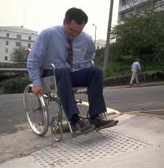 cross walk by curb cut to assist wheelchair