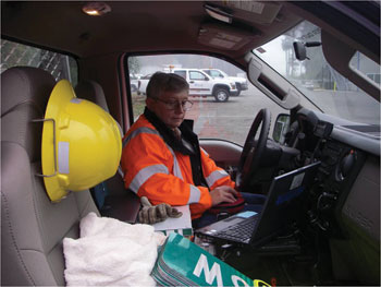 Photo. A sign technician uses a laptop while sitting in the cab of a parked maintenance truck.