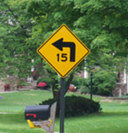 Photo. A yellow advisory sign with a black speed advisory of 15 MPH and curve warning.
