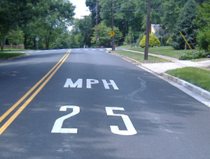 Photo. A pavement marking of '25 MPH' to encourage speed reduction for an impending curve.