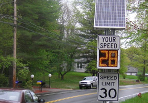 Photo. A solar-powered speed feedback sign. The bottom part of the sign is a typical speed limit sign with a speed limit of 30 MPH. Above that is a changeable display that states 'Your speed 28 MPH' The speed changed based on how fast a vehicle is traveling. Above that is a solar panel to power the sign.