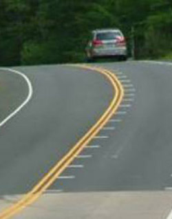 Photo. A rural two-lane road with optical speed bars on the right lane as it approaches a horizontal and vertical curve. The bars are short white lines on either side of the lane and are placed closer together approaching the curve to give the driver the illusion that they are driving faster.