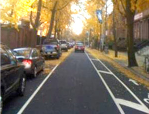 Photo. A street where lane widths were reduced to provide exclusive space for cyclists. Through a reduction in lane width, the road currently has one on-street parking lane, one travel lane, and one bike lane.