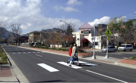 Photo. A crosswalk with a island or median in the center providing a refuge for pedestrians and a shorter distance to cross.