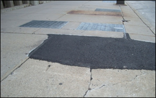 A wedge has been placed to mitigate the hazard caused by a raised sidewalk slab.