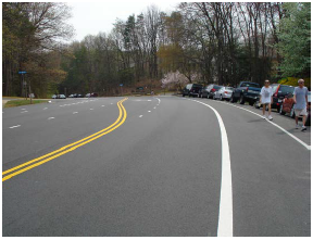 Buffered pedestrian path between on-street parallel parked cars and the travel lane on a roadway with forested areas to either side and no paved side-walk.