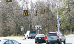 Photo of vehicles turning left at a signalized intersection.