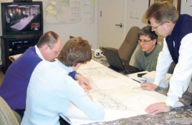 Photo of an RSA team in an office going over road maps and designs.